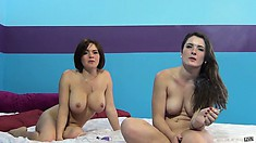 Two horny brunettes sit naked on the bed and talk about what they want