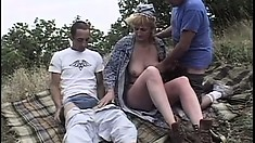 Granny goes for a walk outside and runs into two cocks to play with