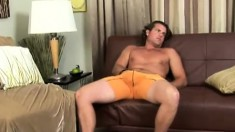 Horny stud removes his orange boxers to masturbate on the couch