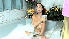 Busty brunette broad with amazing tits soaps herself up in the bath