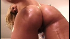 Oiled up blondie with a lot of junk in her trunk mounts a large shaft